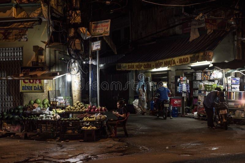 De mensen gaan met hun leven in Ho Chi Minh City, Vietnam, bij nacht stock fotografie