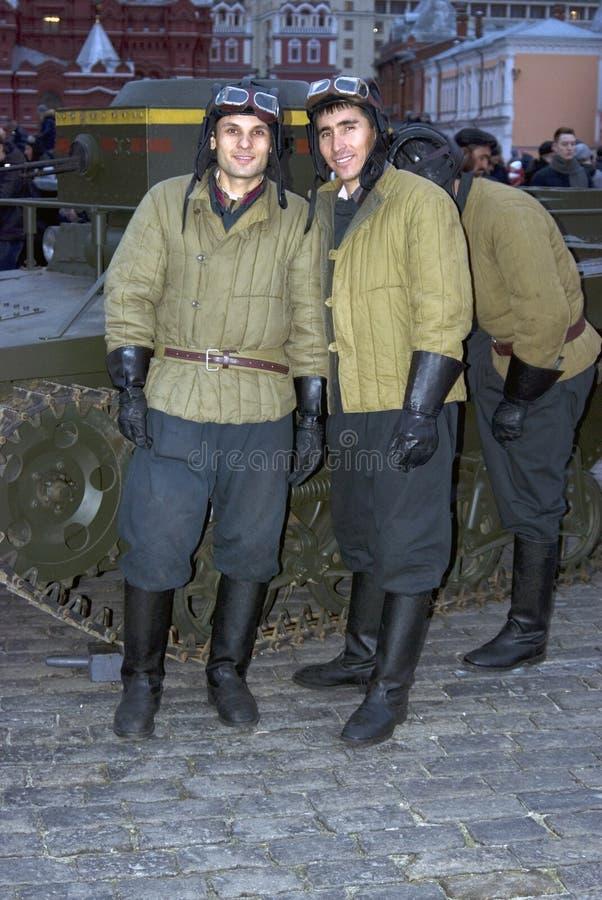 De mensen in gedetailleerde militaire uniformen stellen voor foto's met bezoekers van expositie stock afbeeldingen