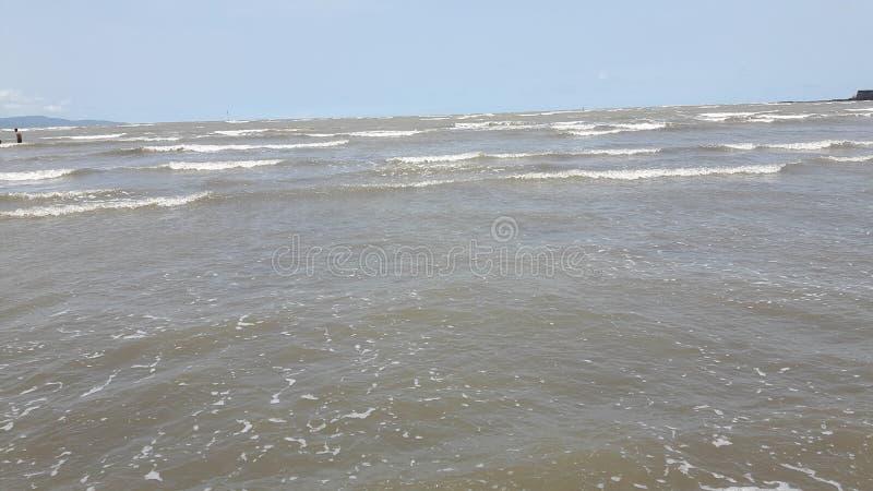 De mensen genieten strand van plaats met blauwe hemel en de wolken stock afbeelding