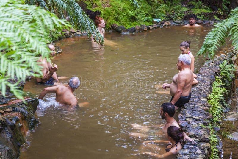 De mensen genieten van bad in natuurlijke thermische pools, de Azoren, Portugal stock afbeeldingen