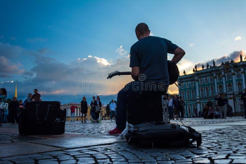 De mensen genieten van de kunst van straatmusicus in het Paleisvierkant, St stock afbeeldingen
