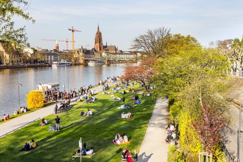 De mensen genieten van de lente bij de rivierleiding in Frankfurt stock afbeelding