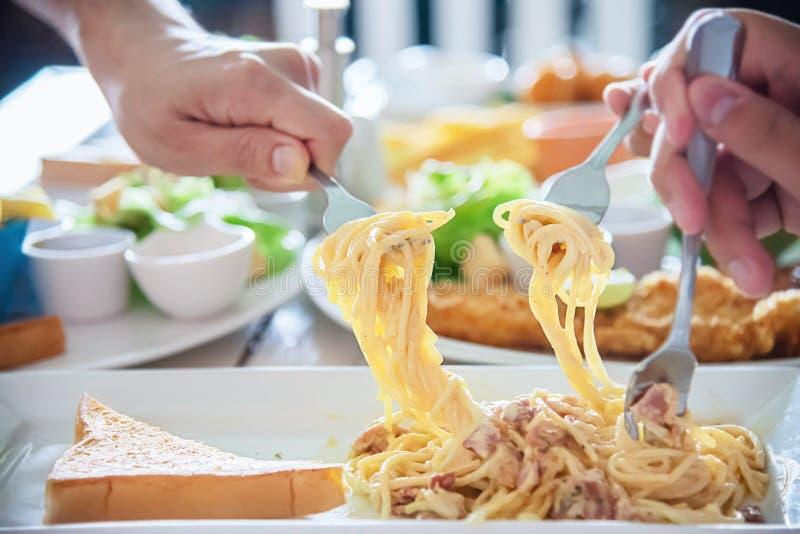 De mensen genieten van eten samen spaghetti in een grote maaltijdreeks stock afbeelding