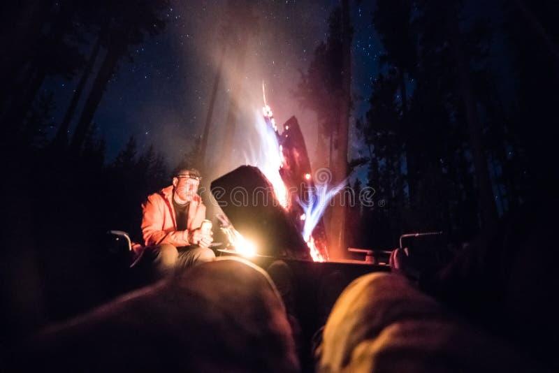 De mensen genieten van het kampvuur bij nachtzitting die en bij kampeerterrein drinken ontspannen stock fotografie
