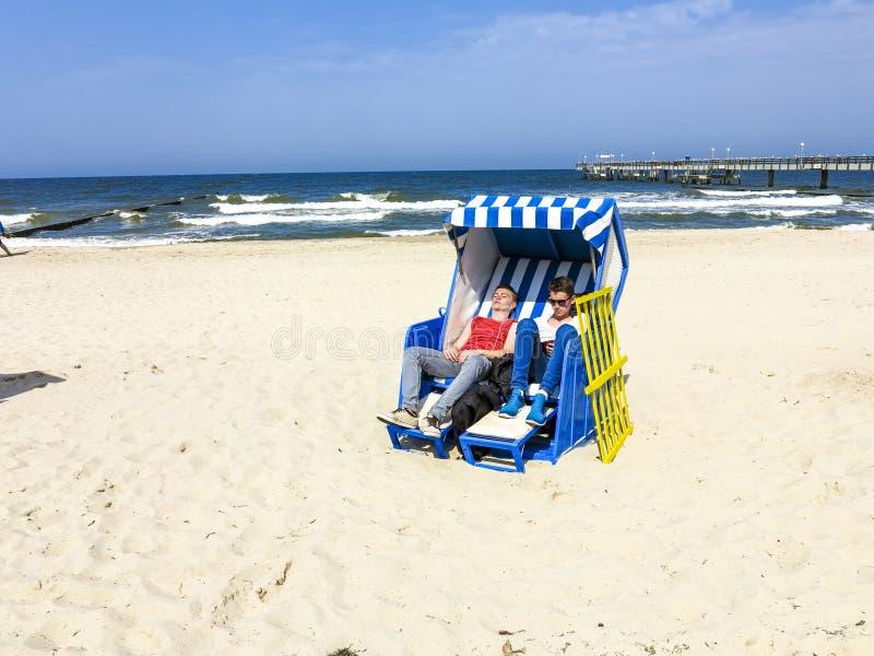 De mensen genieten van sunbath in roofed rieten ligstoel stock afbeeldingen