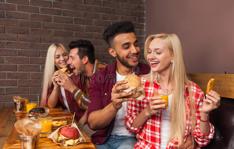 De mensen groeperen het Eten van de Zitting van Snel Voedselburgers bij Houten Lijst in Koffie stock afbeelding