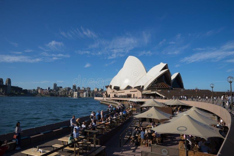De mensen hebben drank en genieten van zonnige dag bij Operabar voor het Operahuis, met een mooie duidelijke blauwe hemel stock fotografie