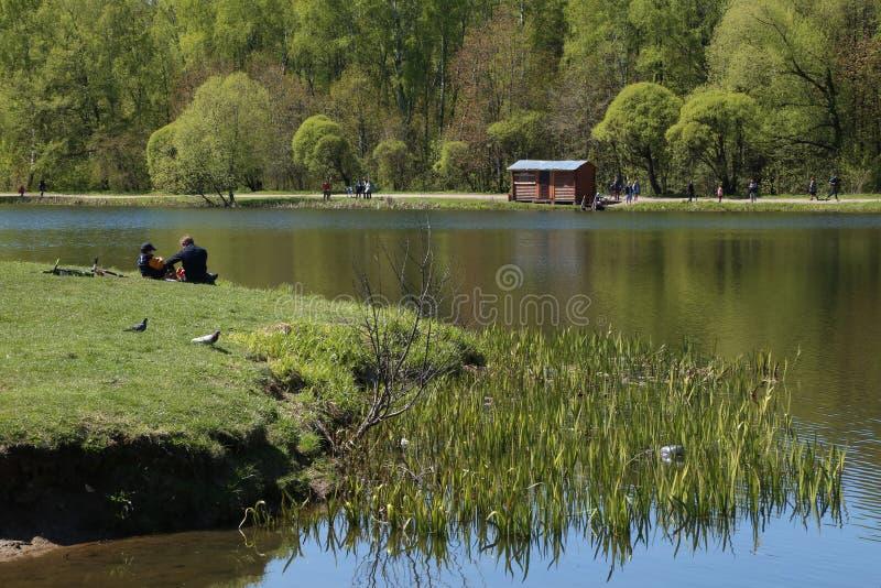De mensen hebben een rust bij het meer in een park van de de lentestad royalty-vrije stock foto