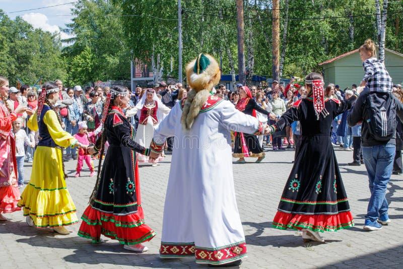 De mensen houden handen, die in een cirkel dansen De jaarlijkse nationale feestdag van Tatars en Bashkirs Sabantuy in het stadspa royalty-vrije stock foto's