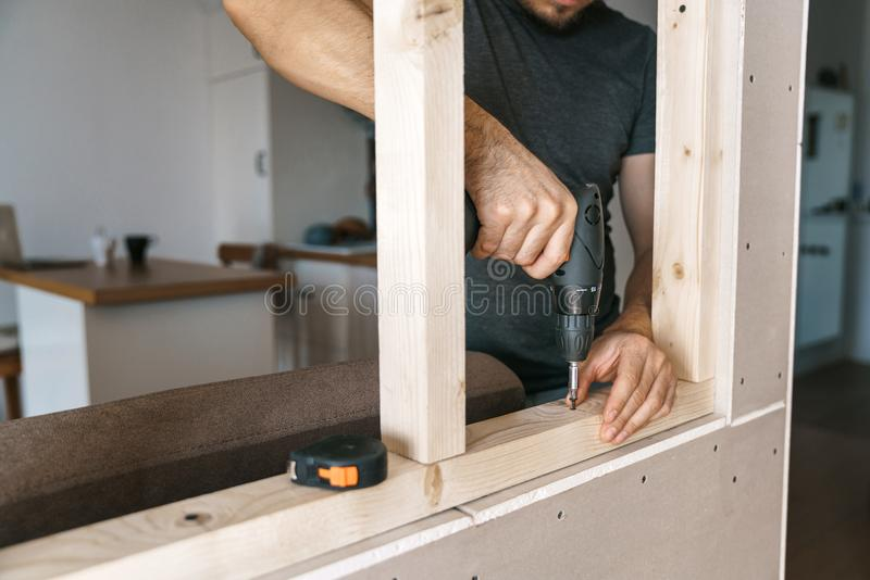 De mensen in huiskleren werken met een schroevedraaier, bevestigend een houten kader voor een venster in hun huis Reparatie zelf royalty-vrije stock foto's