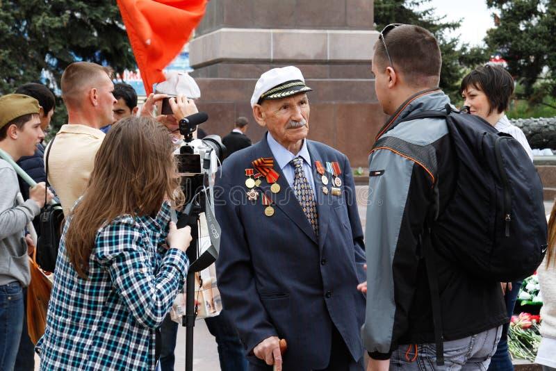 De mensen interviewen een veteraan van Wereldoorlog II op het Vierkant van de Gevallen Vechters in Volgograd royalty-vrije stock fotografie