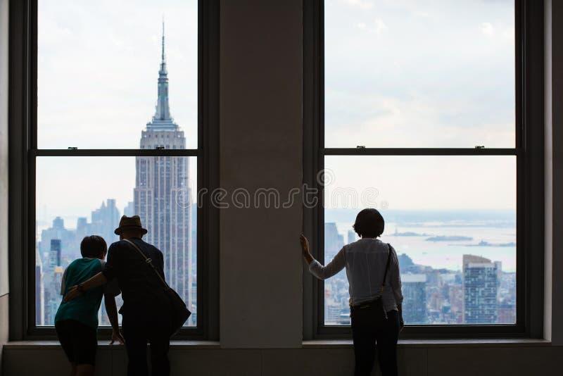 De mensen kijken uit over de Horizon van Manhattan, de Stad van New York royalty-vrije stock afbeelding