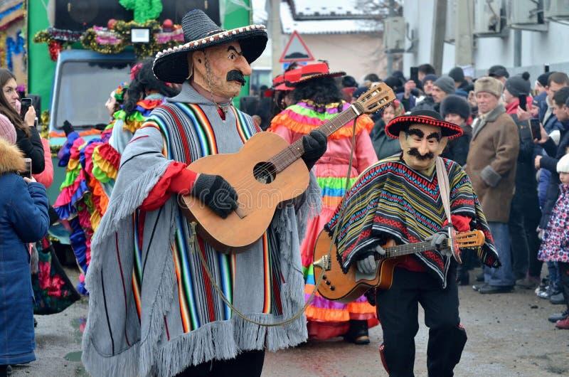 De mensen kleedden zich als Mexicaanse musici in poncho's en sombrero's spelend gitaren bij carniva van de veranderingskleren van royalty-vrije stock afbeelding