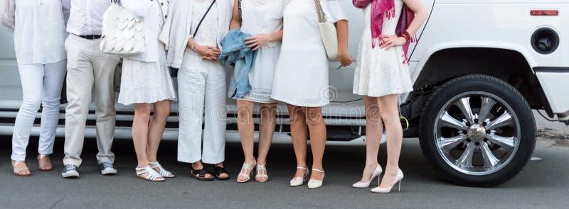 De mensen kleedden zich in het witte stellen naast limousine Lichaamsdelen, witte partij stock afbeelding