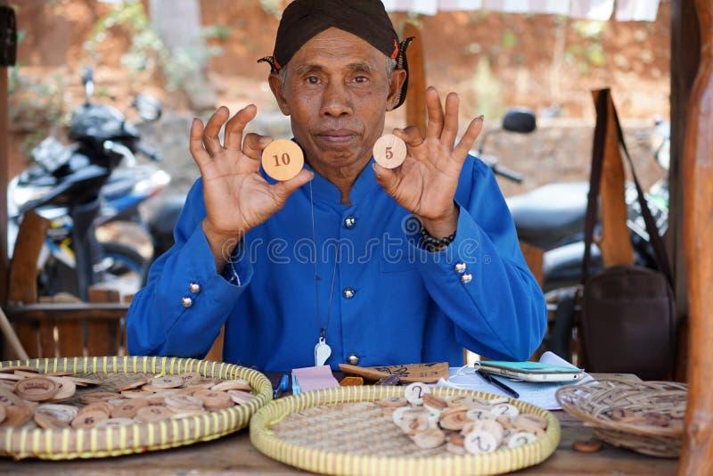 De mensen kleedden zich in Javanese douane die houten muntstukken nummer 10 en 5 houden stock fotografie