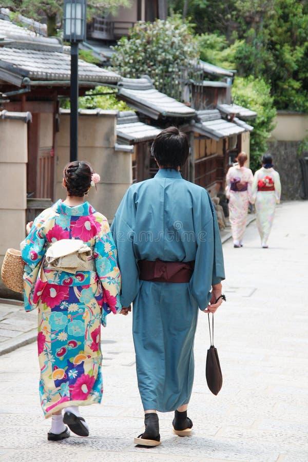De mensen kleedden zich met traditionele Japanse kimono's lopend in van de de stadsgeisha van Kyoto het oude district Japan stock fotografie
