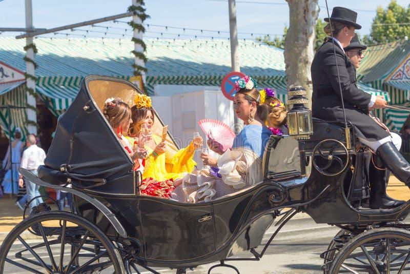 De mensen kleedden zich in traditionele kostuums die paardvervoer en het vieren Sevilla ` s April Fair berijden stock afbeeldingen