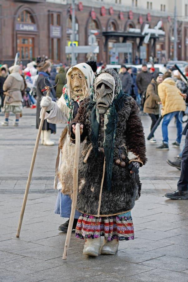 De mensen kleedden zich in uitstekende kostuums en enge maskers bij Russisch nationaal festival ` Shrove ` over Revolutievierkant stock foto's