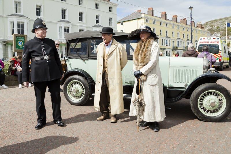 De mensen kleedden zich in Victoriaans kostuum die zich naast een wijnoogst bevinden royalty-vrije stock afbeelding