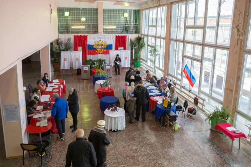 De mensen kwamen in de zaal voor stemming stemmen zijn verfraaid met kleuren van Russische vlag stock fotografie
