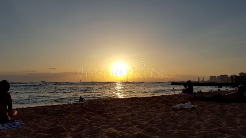 De mensen letten op het dramatische Zonsondergang dalen achter de oceaan royalty-vrije stock foto