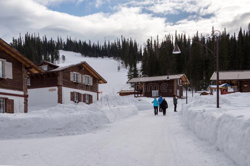 De mensen lopen onder de plattelandshuisjes van de Berg Salanga van de skitoevlucht in de uitlopers van de bergen van Kuznetsk Al royalty-vrije stock fotografie
