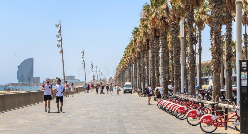 De mensen lopen op het strand van Barcelona aan het eind van D stock fotografie