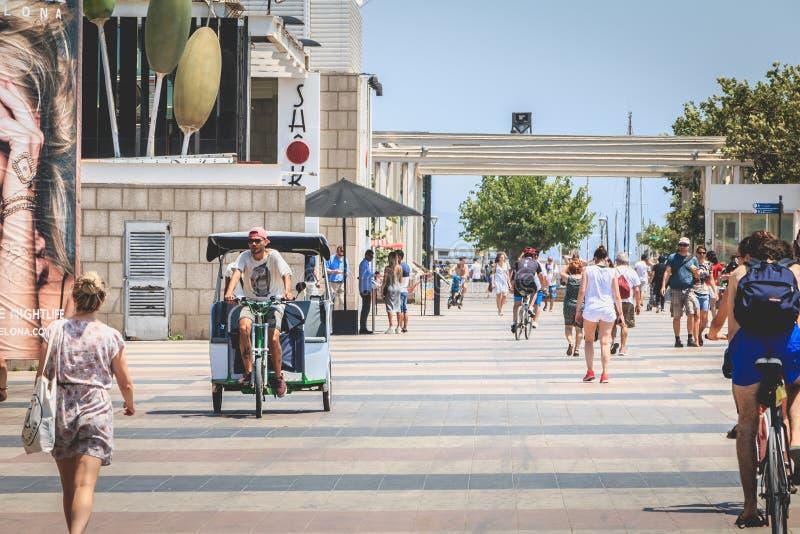 De mensen lopen op het strand van Barcelona aan het eind van D stock afbeeldingen