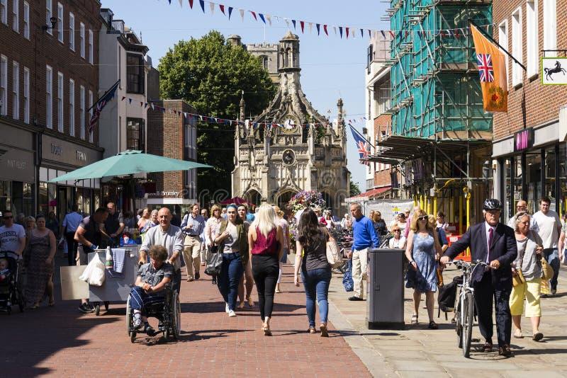 De mensen lopen op straat voor het Kruis van Chichester op 12 Augustus, 2016 in Chichester, het Verenigd Koninkrijk stock afbeeldingen