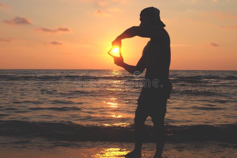 De mensen maken een hoofd-gevormde hand bij zonsondergang royalty-vrije stock afbeeldingen