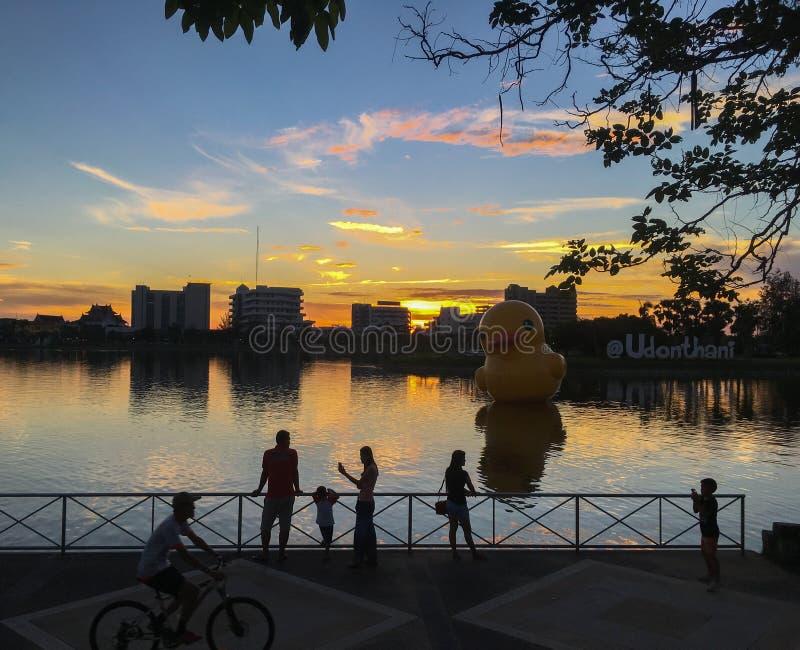 De mensen ontspannen in het meer van Nong Prachak en genieten van met de grote drijvende gele rubbereendenballon royalty-vrije stock afbeeldingen