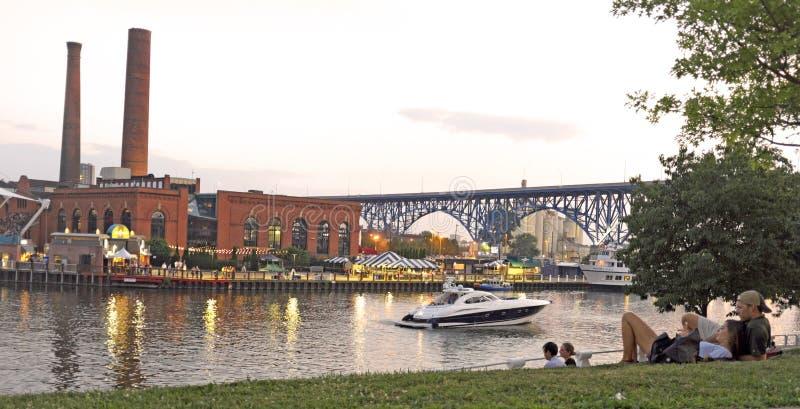 De mensen ontspannen op de bank van het oosten van Cleveland Flats langs de Cuyahoga-Rivier in Cleveland, Ohio, de V.S. stock fotografie