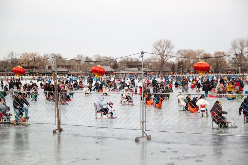 De mensen op het meer bevriezen genieten van sledding, schaats, ijsfiets bij de Zomerpaleis in Peking in de Winter stock fotografie