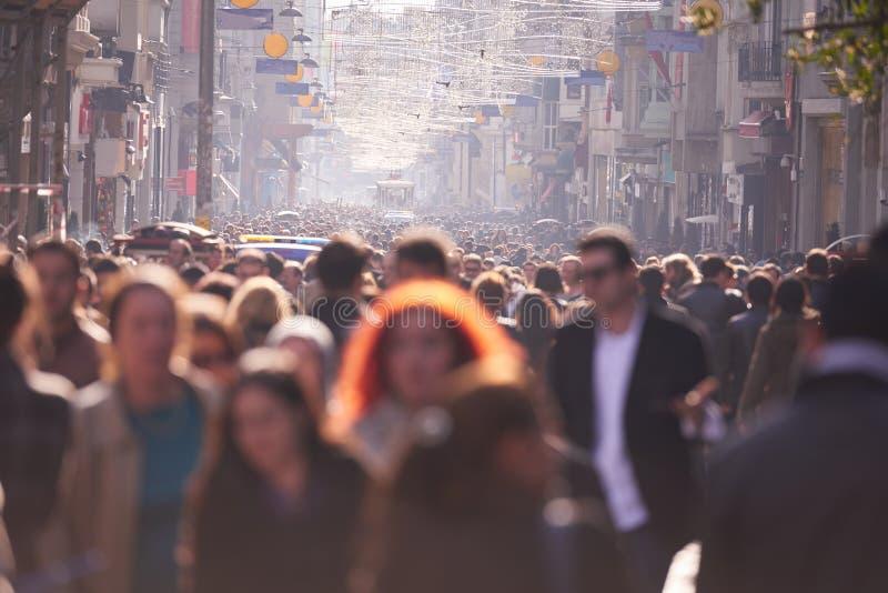 De mensen overbevolken het lopen op straat stock foto's