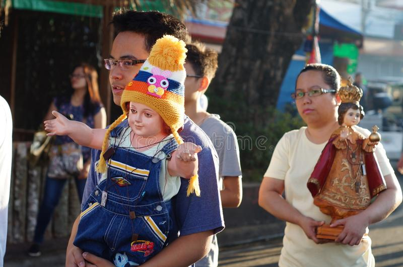 De mensen paraderen de straat die in kleurrijke kostuums dansen, die het pictogram van Zuigelingsjesus dragen om het jaarlijkse s stock fotografie