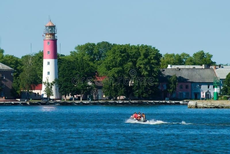 De mensen in rubberboot en vuurtoren zijn Baltiysk royalty-vrije stock afbeeldingen