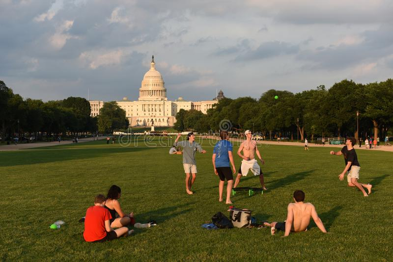 De mensen rusten en spelen de bal op de Nationale Wandelgalerij met het Capitool van Verenigde Staten op de achtergrond stock afbeeldingen