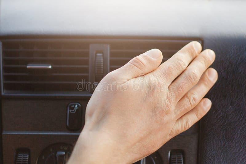 De mensen` s hand op autoverwarmer of veredelingsmiddel, regelt temperatuur in auto terwijl aandrijving Auto` s toebehoren of pan royalty-vrije stock afbeeldingen