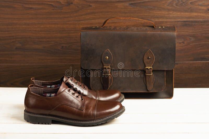 De mensen` s manier met bruine leerschoenen en de zaken doen op een houten achtergrond in zakken Mensen` s manier, schoenen, toeb stock afbeeldingen