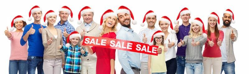 De mensen in santahoeden met verkoop ondertekenen bij Kerstmis stock fotografie