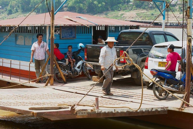 De mensen schepen auto's en motoren aan een lokale veerboot in om Mekong rivier in Luang Prabang, Laos te kruisen stock fotografie