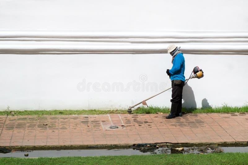 De mensen scherp gras van de grasmaaimachinearbeider royalty-vrije stock fotografie