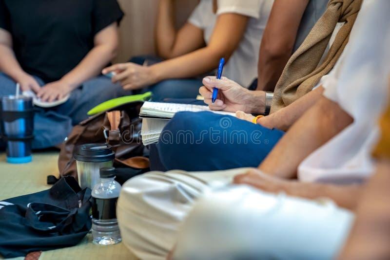 De mensen schrijven iets op het notitieboekje in de sectie van de de sociale klassenlezing van Eco stock afbeelding