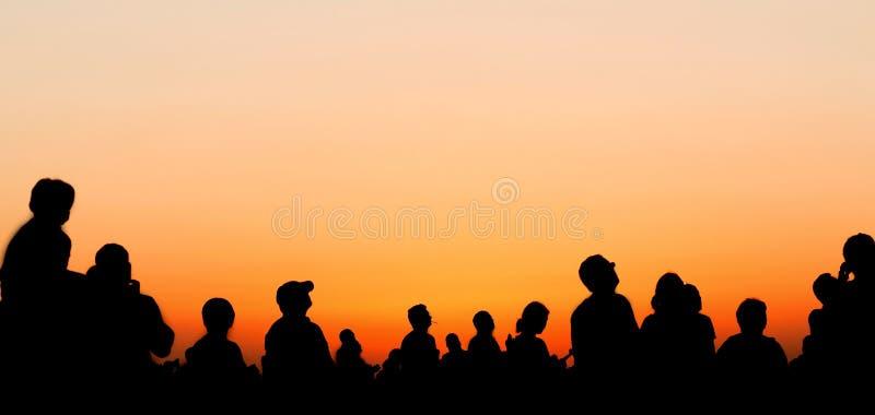 De mensen silhouetteren het letten op zonsonderganghemel