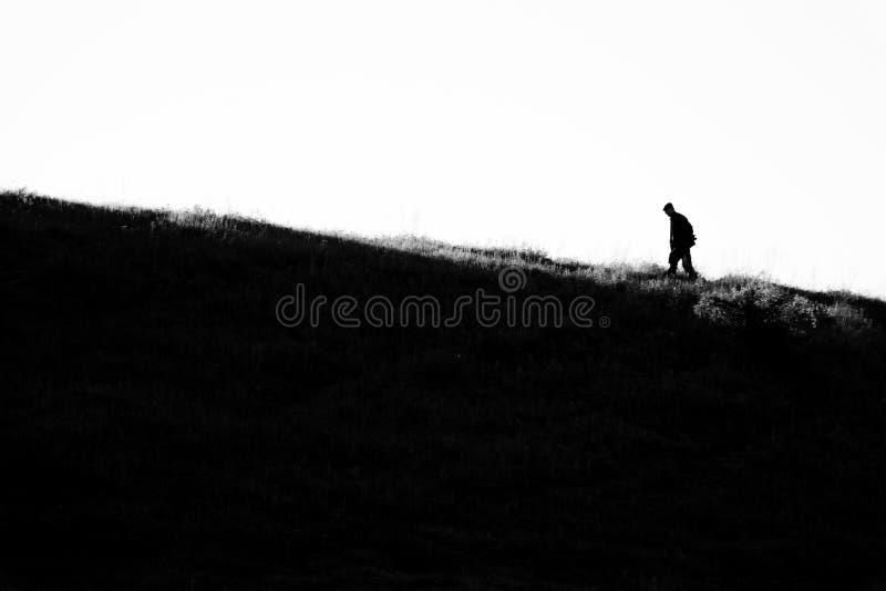 De mensen silhouetteren omhoog het lopen van de heuvel stock foto