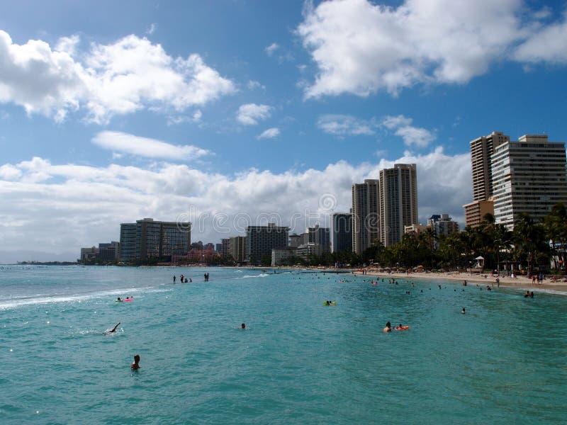 De mensen spelen in het beschermde water en hangen uit op het strand binnen royalty-vrije stock fotografie