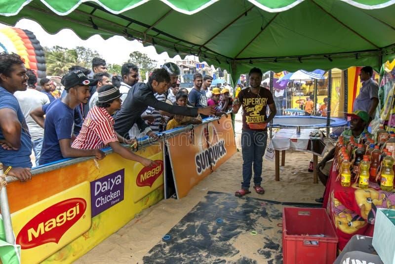 De mensen spelen hoepels bij een opstelling van de showtent op Negombo-strand in Sri Lanka stock foto's