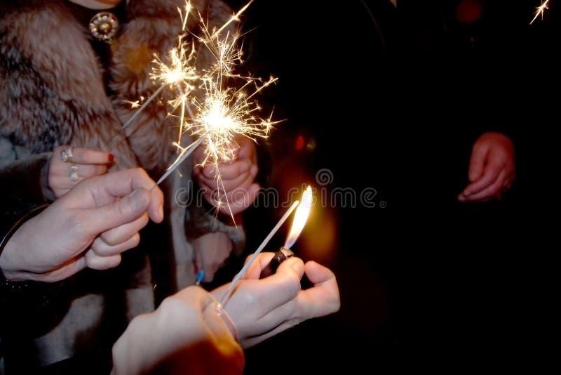 De mensen staken de sterretjes onder de chiming klok voor het nieuwe jaar aan stock foto's