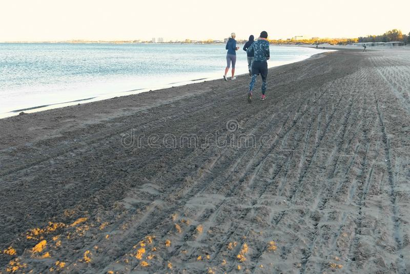 De mensen stoten op het zandstrand aan door het overzees bij zonsopgang in de herfst, achtermening stock afbeelding