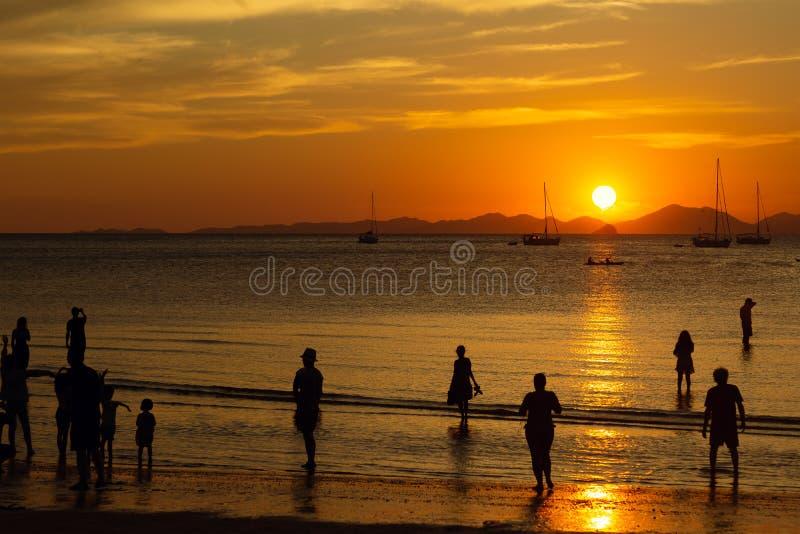 De mensen, toeristen genieten van een schitterende zonsondergang op een tropisch strand De silhouetten van mensen allen letten op stock foto's